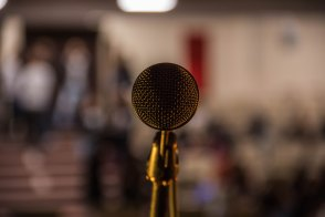 Photo of a mic facing towards the camera with a blurred out crowd in the background. Source: https://unsplash.com/photos/c4lXkCHuaXY